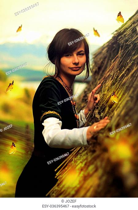 A beautiful young woman with dark hair, black velvet historical dress and a subtle smile is touching gently the rough surface of an ancient straw house roof