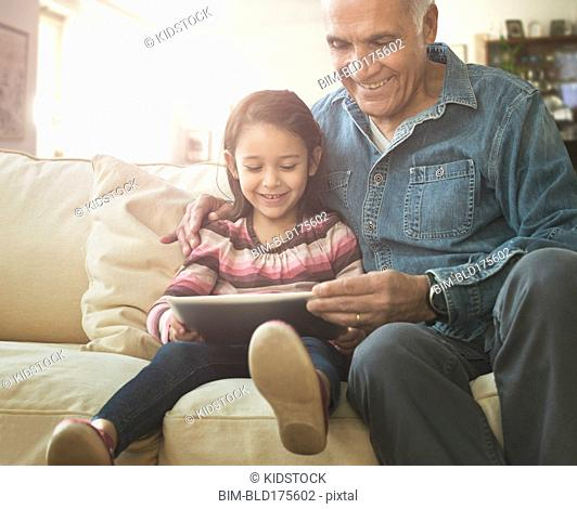 Grandfather reading to granddaughter on sofa