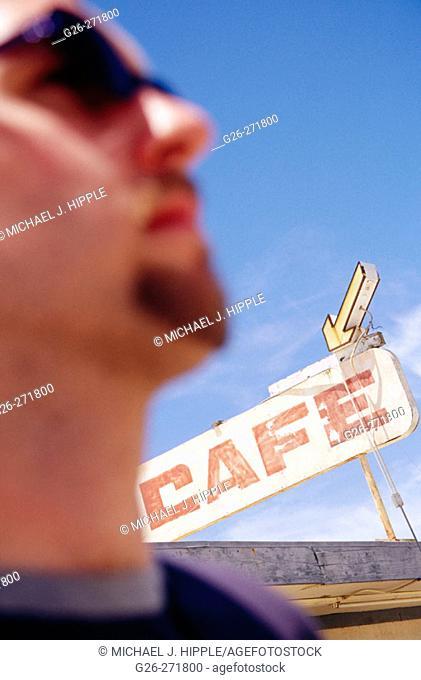 Blurred man and abandoned café sign. The Salton Sea. California. USA