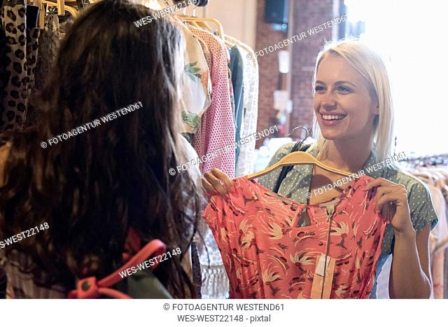 Happy young woman shopping for new clothes with friend