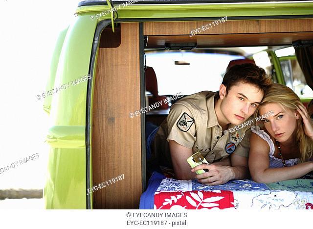 Couple lying in back of van