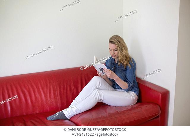 Pretty blonde woman reading a book on the couch