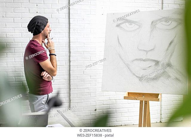 Artist looking at drawing in studio