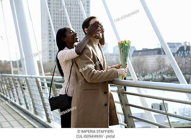 Man standing on bridge, holding flowers, woman surprising him, covering his eyes from behind