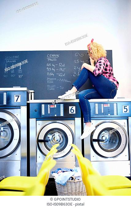 Female laundrette owner sitting on top of washing machine writing on chalkboard