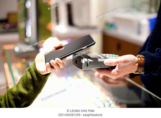 Woman pay by mobile phone in optical shop