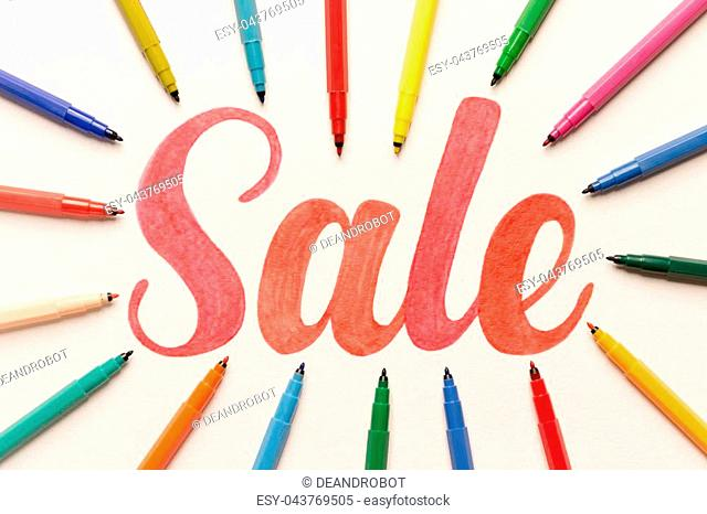 Red hand written calligraphy lettering 'Sale' in bunch of colorful markers on white paper