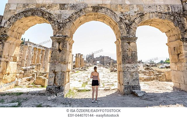 Woman stands near Byzantine Gate at Hierapolis ancient city in Pamukkale, Turkey