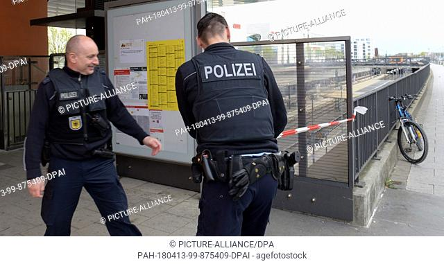 13 April 2018, Germany, Neu-Ulm: Police cordoning off the entrance to the train station. A 500kg bomb from the second world war was found at a construction site...