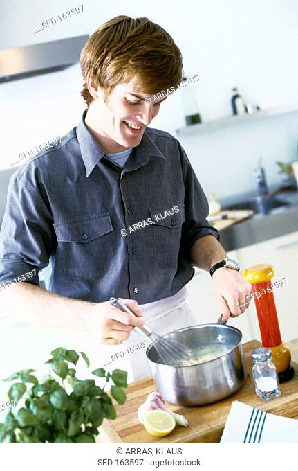 Young man stirring soup with whisk