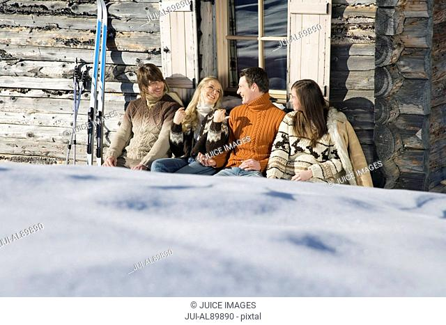 Two couples sitting outside chalet in winter