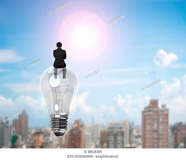 Businessman sitting on light bulb, on sunny sky cityscape background