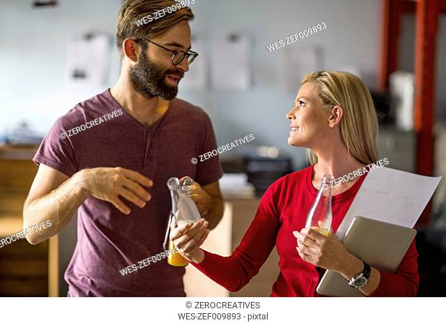 Man and woman discussing in warehouse holding juice bottles
