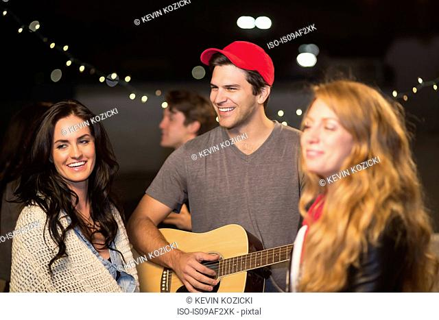 Young adult friends enjoying guitar music at rooftop party