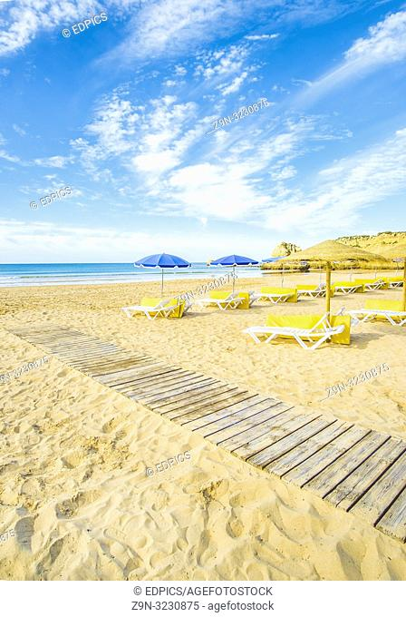 umbrellas and beach chairs at deserted beach in pre-season, praia da rocha, portimao, algarve, portugal