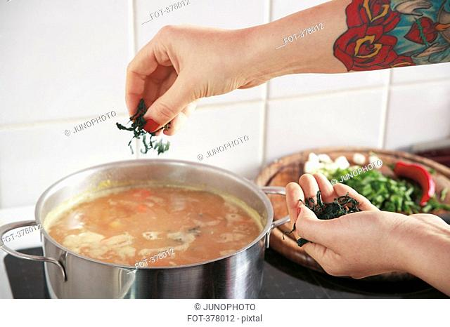 Woman sprinkling ingredient into soup