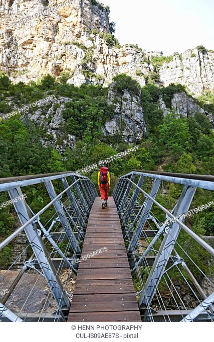 Hiker on hanging footbridge over the Verdon canyon, Provence, France