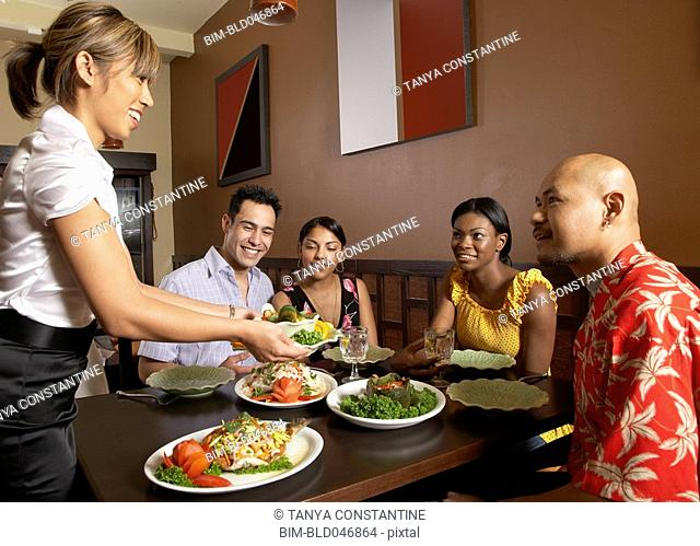 Asian female server bringing food to table