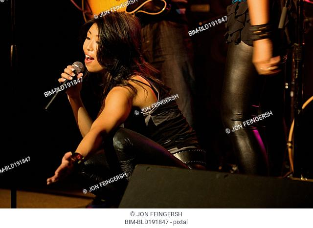 Asian woman singing onstage