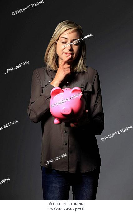 Young woman with money pig