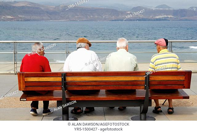 Four elderly men sitting on bench at coast In Spain