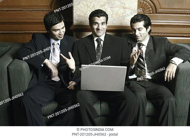 Three businessmen sitting on a couch with a laptop