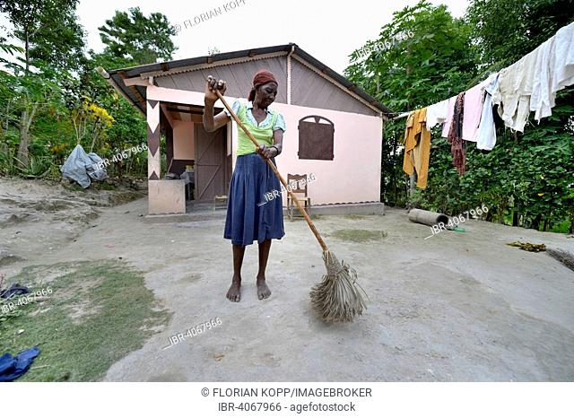 Elderly woman sweeping the courtyard in front of the house which she received from a relief organisation after the 2010 earthquake, Cotes-de-Fer