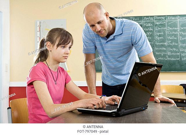 A schoolgirl using a laptop with a teacher standing beside
