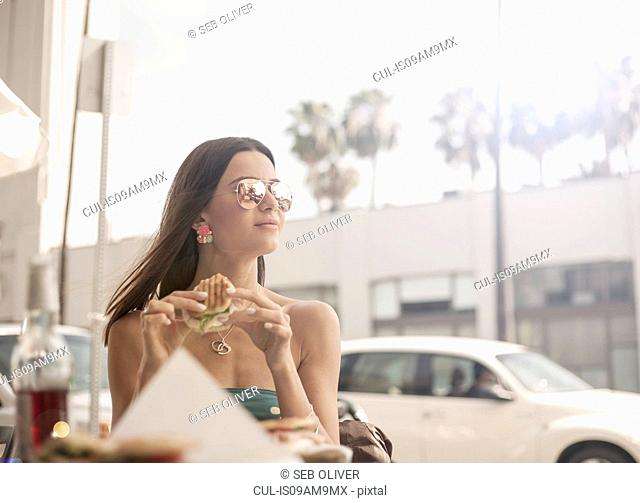 Young woman sitting at outdoor table, eating sandwich