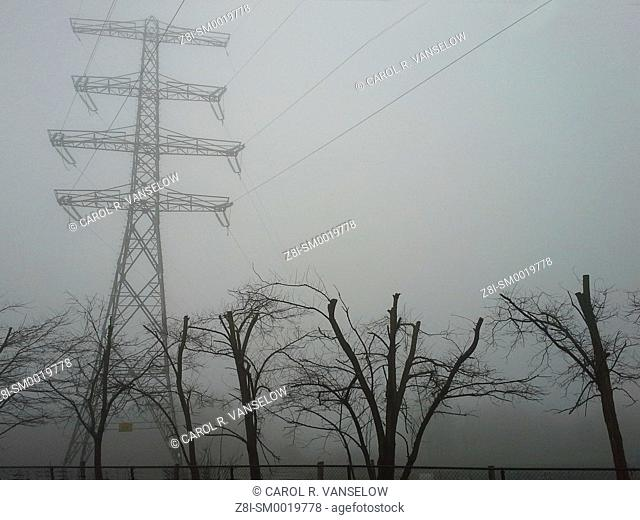 electrical pylon in field on a foggy day. Shot taken in Limburg province of the Netherlands