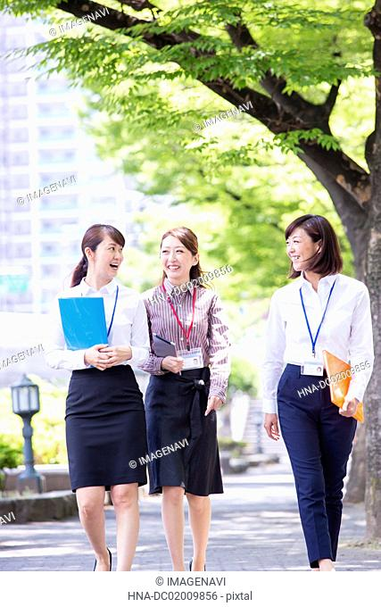 Business women walking along with tree-lined road