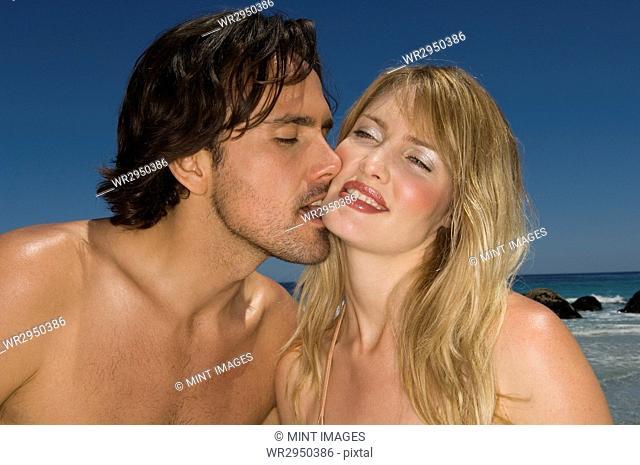 Couple on a beach, man kissing woman's chin