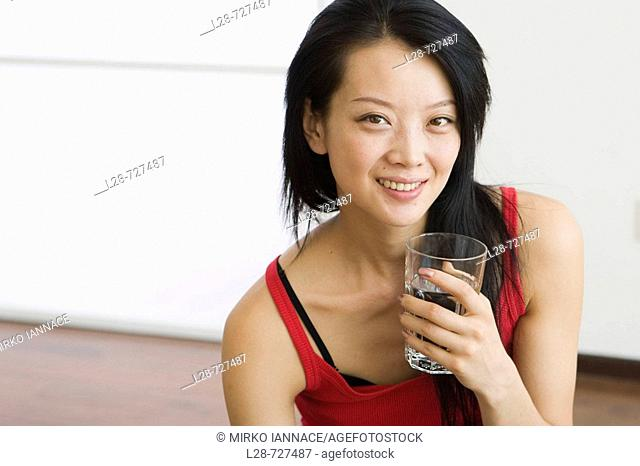 Young woman sitting on water, holding glass of water, smiling