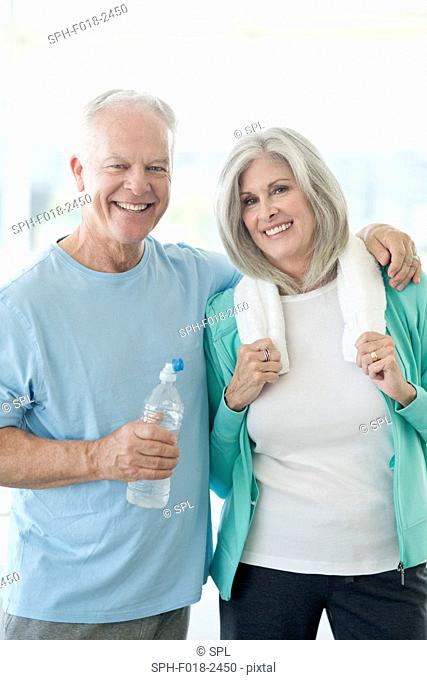 Senior couple in gym, smiling