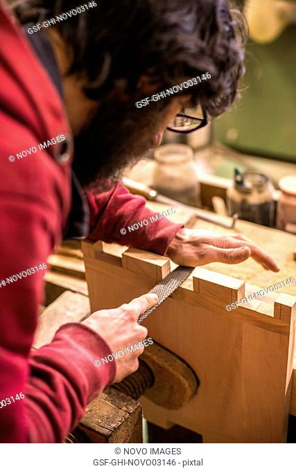 Woodworker Filing Dovetails in Piece of Wood, Close-Up