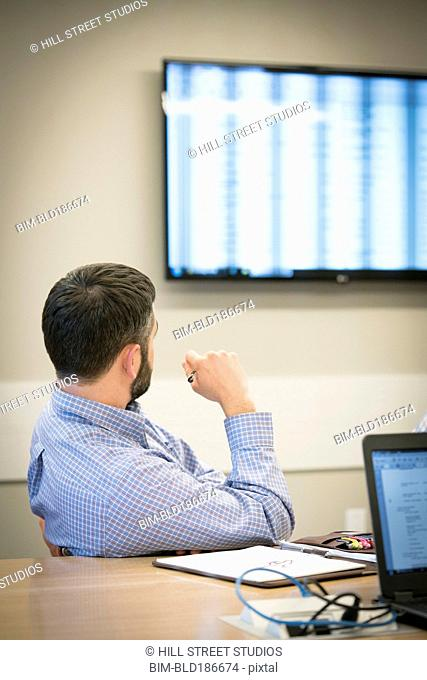 Caucasian businessman watching monitor in office meeting