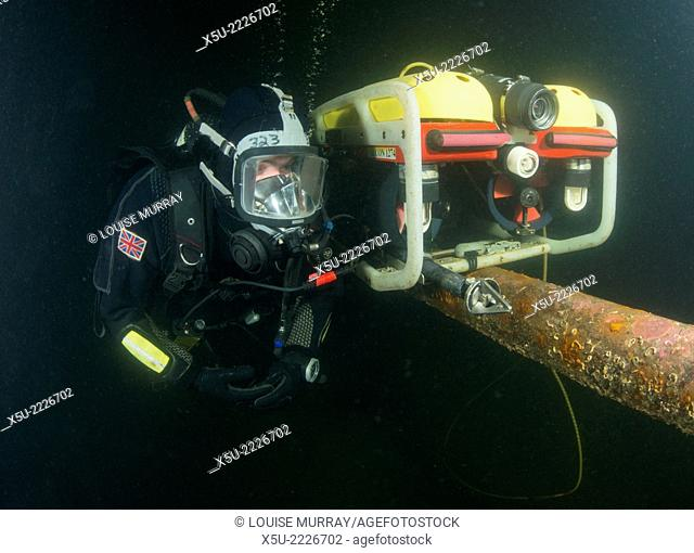 Commercial scuba diver in Full face AGA mask with communications links to surface, with underwater robot or ROV