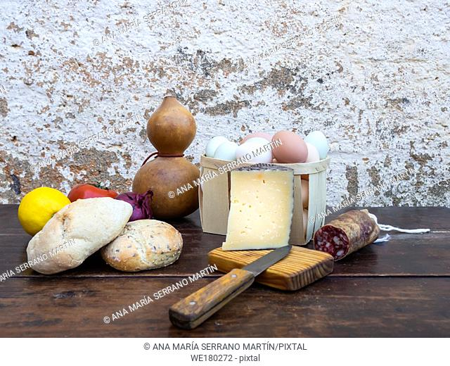 Traditional spanish food on an old wooden table, Iberian pork sausages, bread, eggs, cheese and vegetables and an old knife