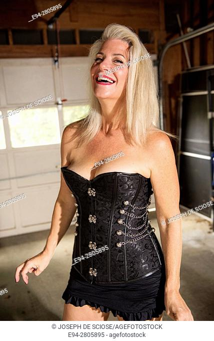 A 52 year old blond woman wearing a corset smiling at the camera, indoors