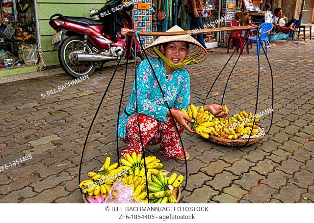 Woman on street in Saigon Ho Chi Minh City with fruit on baskets on shoulder