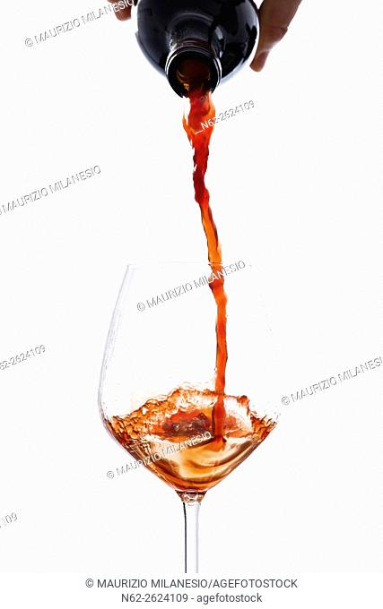 Wine poured from a bottle into a wine glass, on a white background
