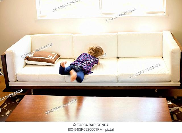 Girl playing on sofa in living room