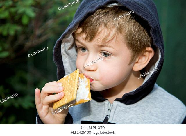 Young boy trying to eat a sticky s'more outdoors; Edmonton, Alberta, Canada