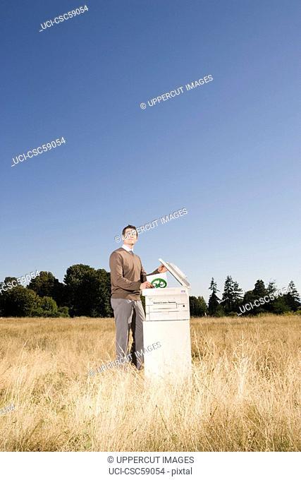 Businessman next to copier in field