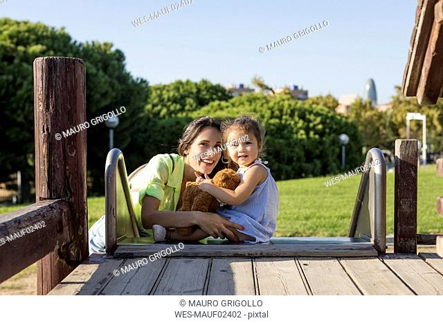 Smiling mother with daughter on slide on a playground