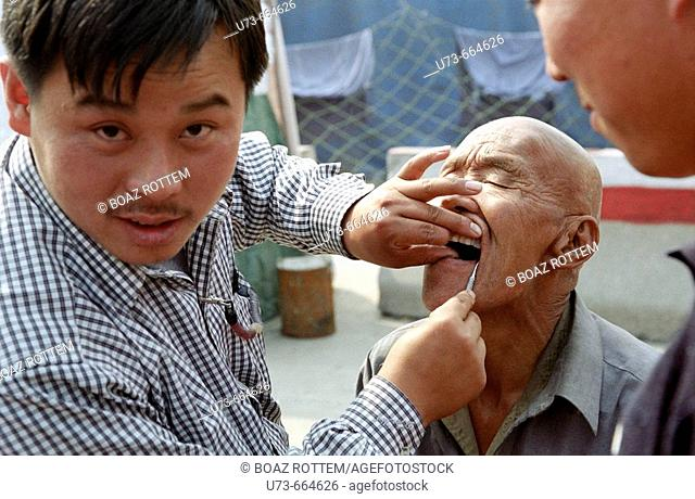 Going to the dentist in a local market is a common scene in rural China