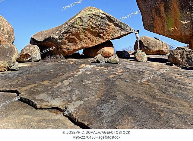 Woman tourist playing around rock formations, Matopos, Zimbabwe