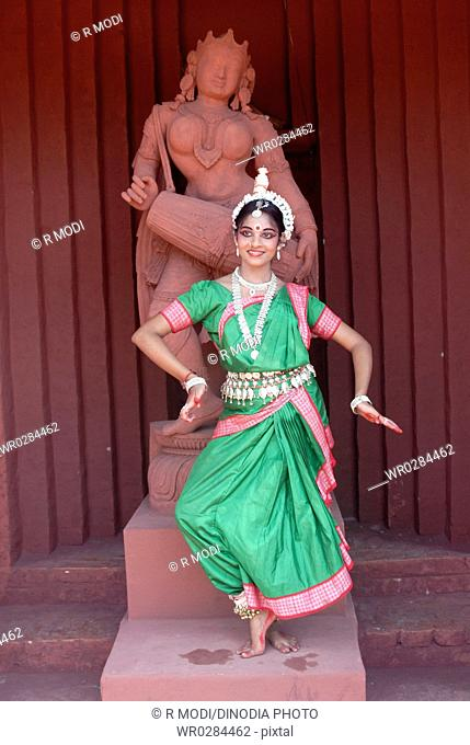 Woman performing classical traditional Odissi dance in front of statue on stage MR736D