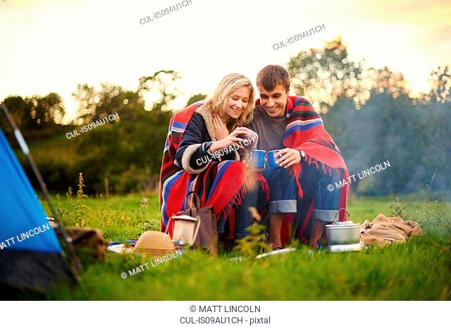 Young camping couple drinking tea