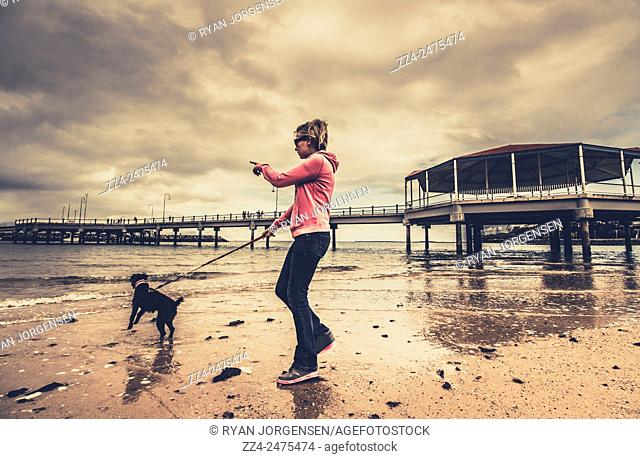 Authentic candid instagram style portrait of a blonde woman in mid twenties pointing while leading pet dog on leash. Redcliffe jetty, QLD, Australia